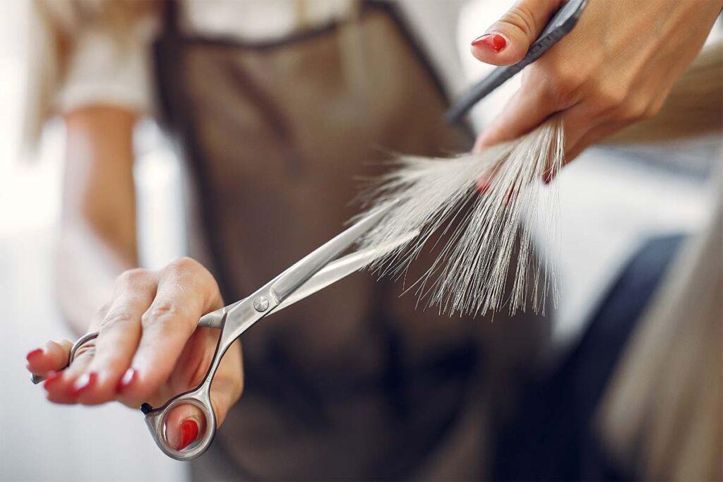 Coiffeur en train de couper les pointes de cheveux