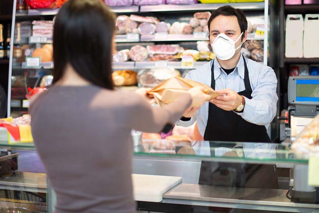Boucher donnant sa commande à une jeune femme en respectant les gestes barrières anti-covid 19