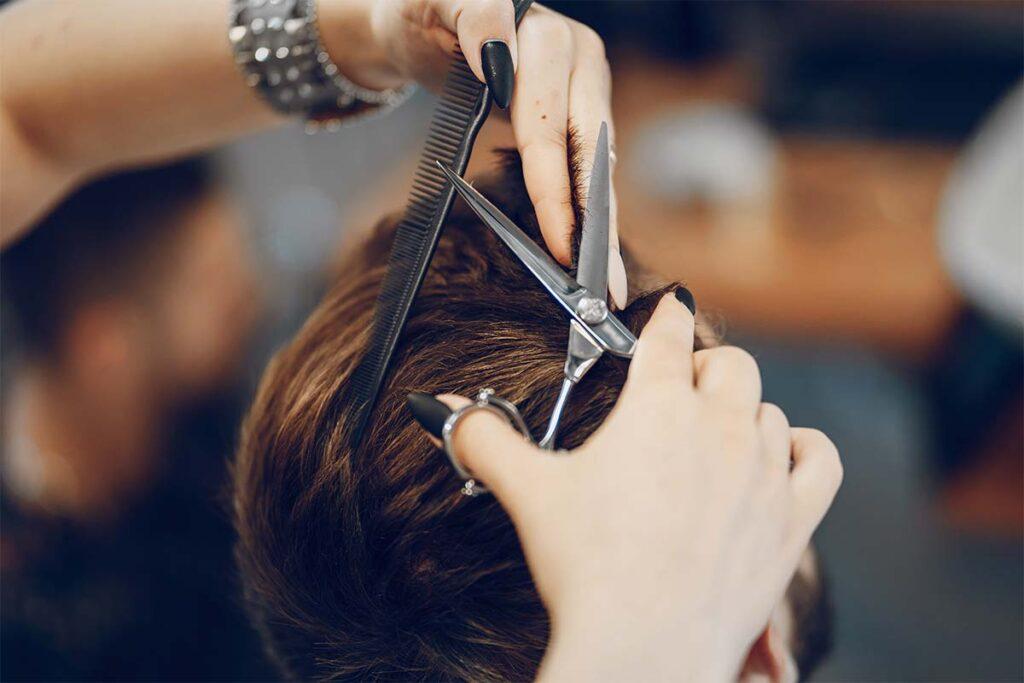 Homme en train de se faire couper les cheveux chez le coiffeur