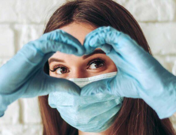 jeune femme faisant un coeur avec ses doigts en portant un masque covid 19