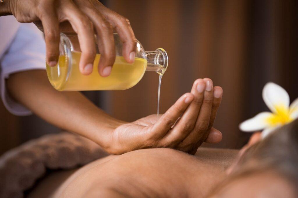 Une masseuse professionnelle fait couleur de l'huile de massage dans sa main