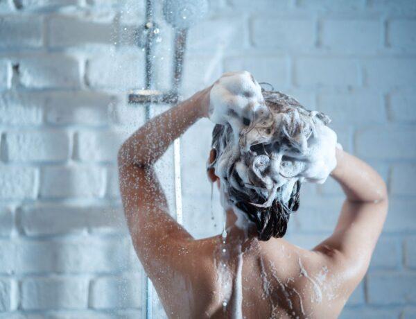 Femme se lavant les cheveux avec un shampoing sec dans une douche