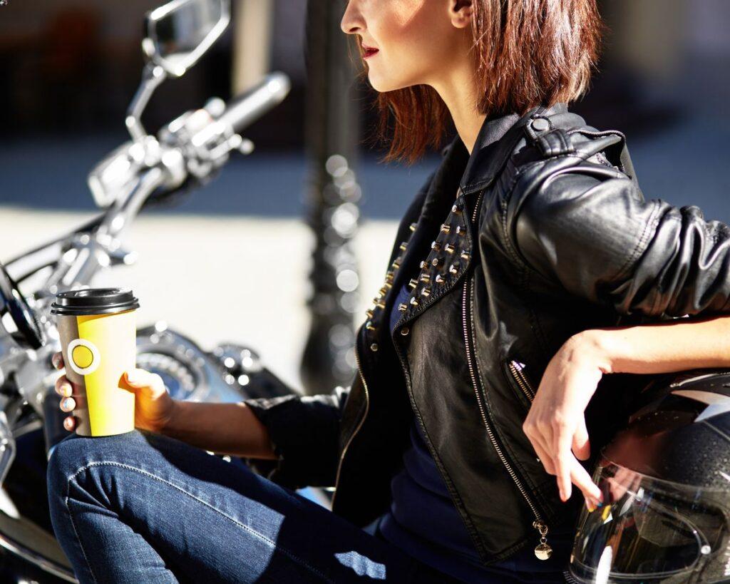 Jeune femme avec veste en cuir et clous sur une moto tenant un café.