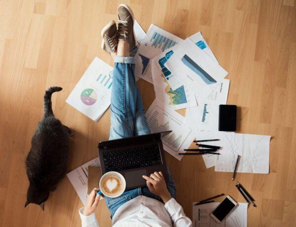 Jeune femme assise par terre pendant le télétravail avec des documents et un chat